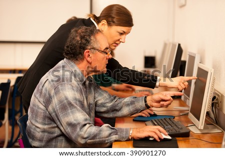 Group of adults learning computer skills. Intergenerational transfer of knowledge. - stock photo