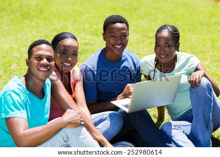 group of african american college friends sitting together at the park - stock photo