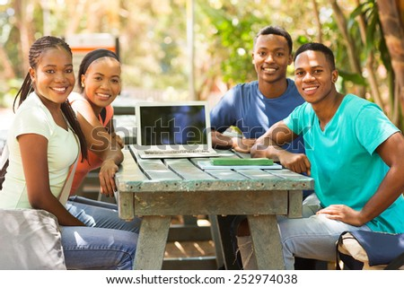 group of african college friends sitting together outdoors - stock photo
