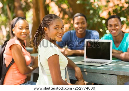 group of african college student relaxing outdoors and looking at the camera - stock photo