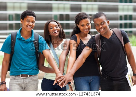 group of african college students putting hands together - stock photo