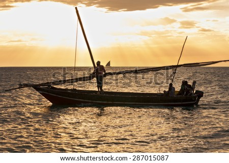 group of african fishermen returning home after a days fishing the sun is setting on a golden sea and distant horizon