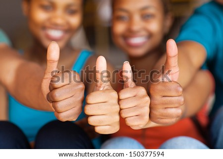 group of african friends thumbs up closeup - stock photo