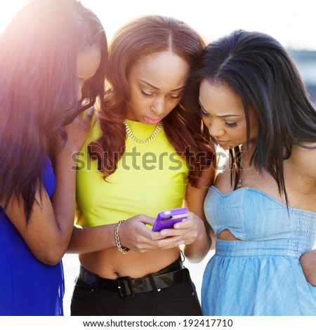 group of african girls looking at smart phone together - stock photo
