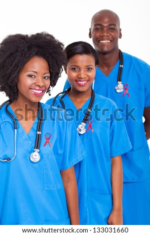 group of african medical workers with red ribbon for HIV awareness - stock photo