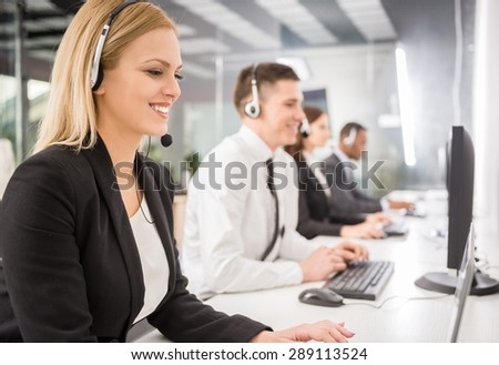 Group of agents sitting in line in a bright call centre. - stock photo
