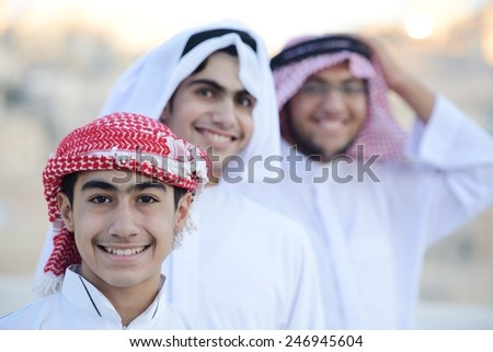 Group of Arabic boys standing in line and pointing - stock photo