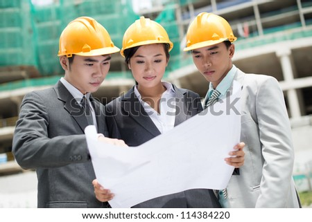 Group of architects being busy studying blueprint - stock photo