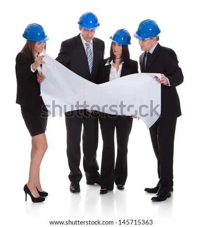 Group Of Architects Discussing Blueprint Over White Background