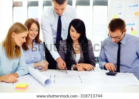 Group of architects discussing new project at office - stock photo