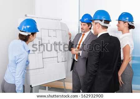 Group Of Architects Discussing Plan Drawn On Blueprint At Office