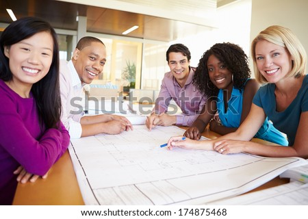 Group Of Architects Discussing Plans In Modern Office - stock photo