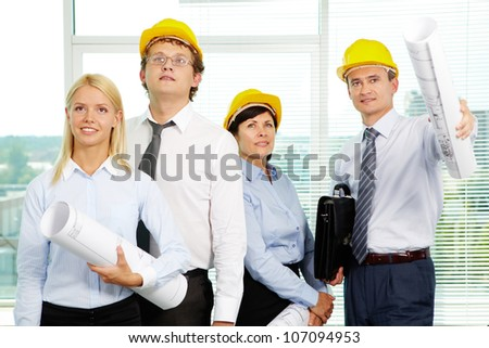 Group of architects in helmets interacting in office