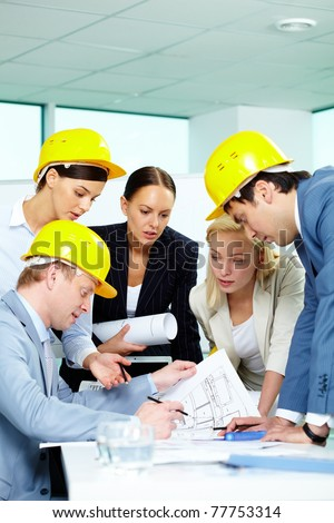 Group of architects looking at a project and discussing it - stock photo