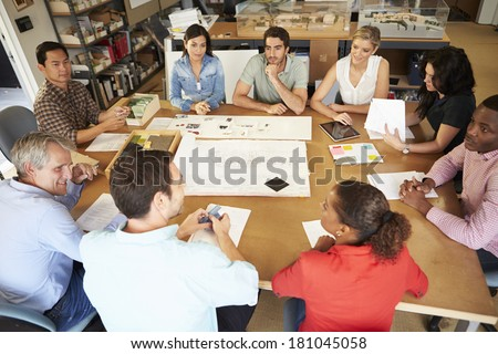 Group Of Architects Sitting Around Table Having Meeting - stock photo