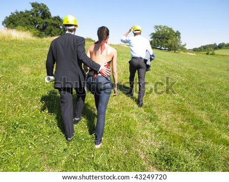 Group of architects walking through a meadow and wearing yellow hard hats. Horizontal. - stock photo
