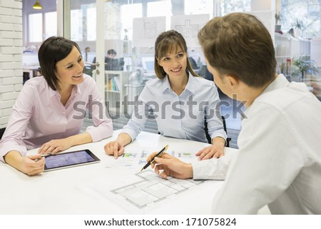 Group of architects working in office on tablet pc and plans - stock photo