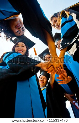 Group of Asian graduation students touching hands together - stock photo