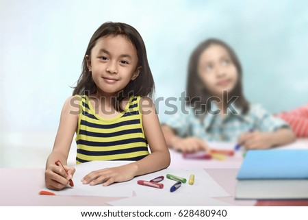 Group of asian little girl at the table and drawing with crayon in the classroom