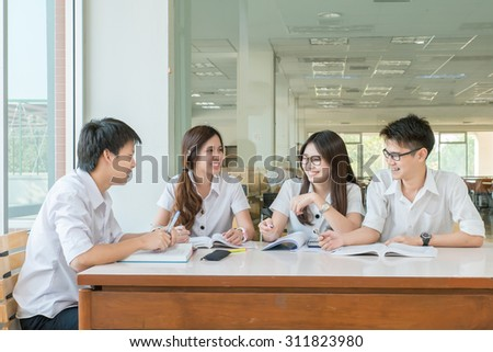 Group of Asian students in uniform studying together at classroom.   - stock photo