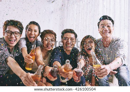 Group of Asian young people clinking bottles of beer with you - stock photo