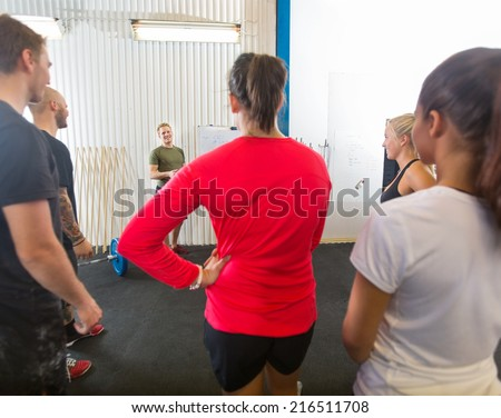 Group of athletes listening to instructor at cross training gym - stock photo