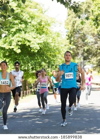 Group of athletes running in marathon on street - stock photo