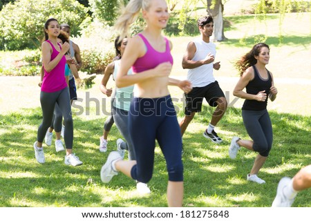Group of athletes running on grassy land in park - stock photo