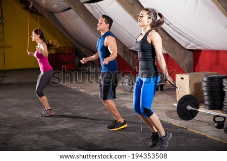 Group of athletic people using jump ropes for their workout in a cross-training gym - stock photo