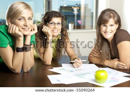 Group of attractive businesswomen leaning on hands at meeting room table, smiling. - stock photo