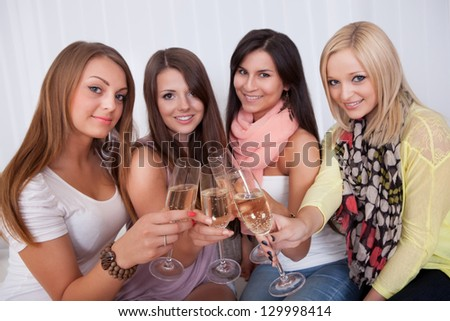 Group of attractive stylish girls with lovely smiles standing close together toasting with champagne - stock photo