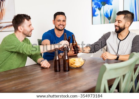Group of attractive young men making a toast with beer while hanging out at home - stock photo