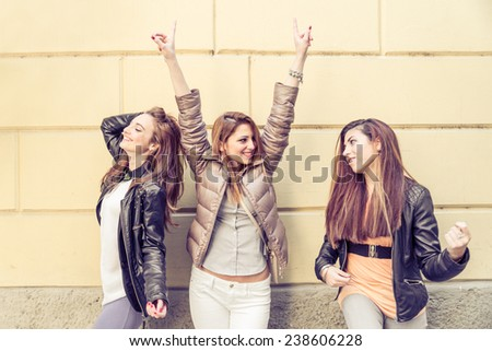 Group of attractive young women  having fun outdoors - Three playful girls singing and dancing - Fashion models posing - stock photo