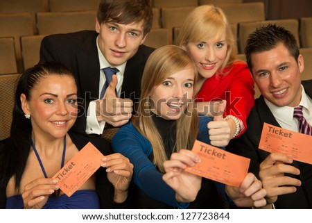 Group of audience members in a theater, on a concert or in a cinema presenting tickets or admission passes - stock photo