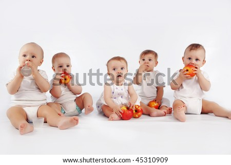 Group of babies with apples sitting on white studio background - stock photo