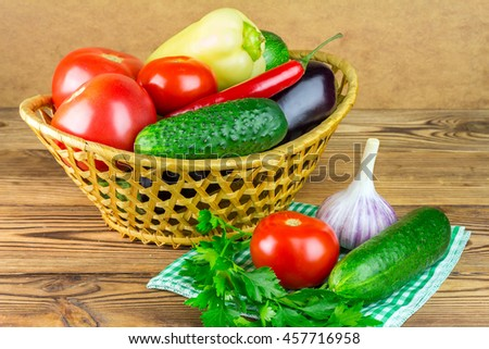 Group of backyard vegetables, tomato, cucumber, peppers, garlic, eggplant in wicker basket on wooden background - stock photo
