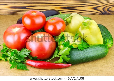 Group of backyard vegetables, tomato, peppers, cucumber, zucchini, eggplant and parsley on wooden background - stock photo