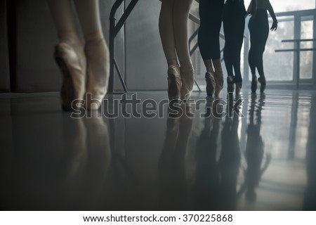 Group of ballet dancers stands near the ballet barre at the ballet hall against the big window. Daylight falls on them. Shoot from a low angle. - stock photo