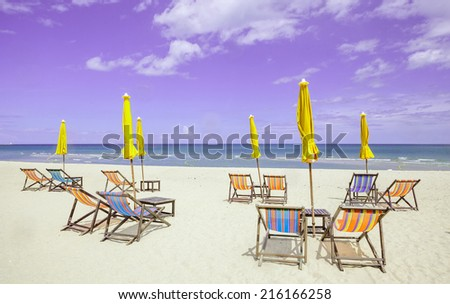 Group of beach chairs and closed umbrellas on white sand beach with cloudy sky. Concept for rest, relaxation, holiday. - stock photo