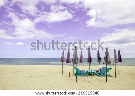Group of beach chairs and closed umbrellas on white sand beach with cloudy sky. Concept for rest, relaxation and holiday in Thailand. - stock photo