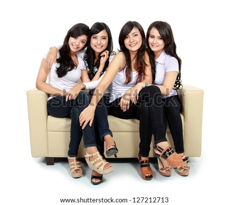 Group of beautiful asian women smiling together sitting on the couch isolated over white background