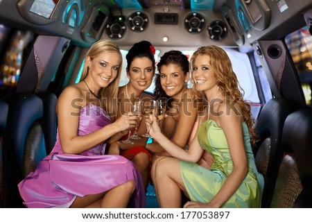 Group of beautiful elegant smiling girls celebrating in limousine.