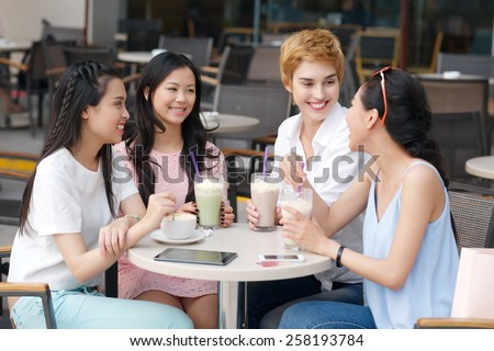 Group of beautiful female friends talking in the cafe
