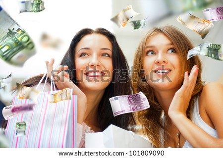 Group of beautiful shopping women with bags and smiling. Money flying around them. Spending money non stop concept - stock photo