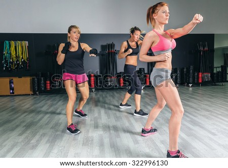 Group of beautiful women in a hard boxing class on gym training punch - stock photo