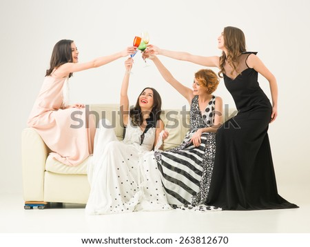 group of beautiful women sitting together on sofa celebrating with drinks - stock photo