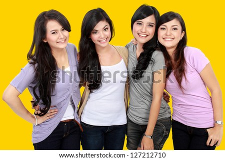 Group of beautiful women smiling isolated over a yellow background