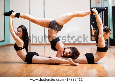 Group of beautiful women taking stretching to a whole new level in a pole dancing class