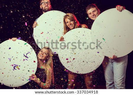 Group of beautiful young people celebrating New Year's Eve, holding four blank cardboard circles - stock photo