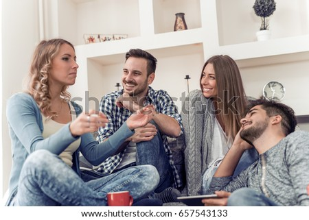 Group of beautiful young people enjoying in conversation and drinking coffee